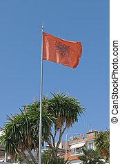 Fluttering Albanian flag blue sky in background
