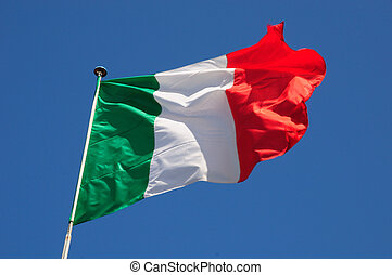 Italian flag fluttering in a brisk breeze against a bright blue sky.