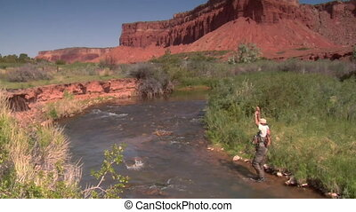fly fisherman catches trout with red rock cliffs in distance