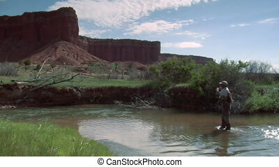 fly fisherman in stream with red rock cliffs