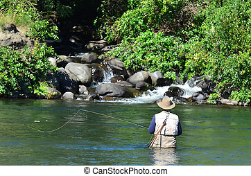 A fisherman fly fishes for Trout fish in Tongariro river near Taupo lake, New Zealand.