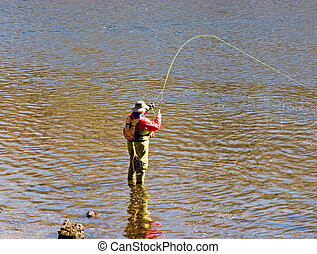 A fly fisherman 'playing' a trout on his fly line