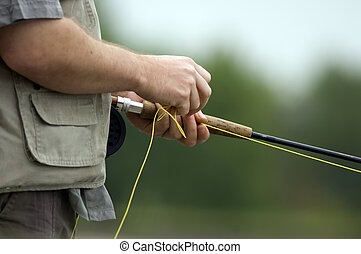 Fly fishing - Close up of a mans hands feeding out line ...