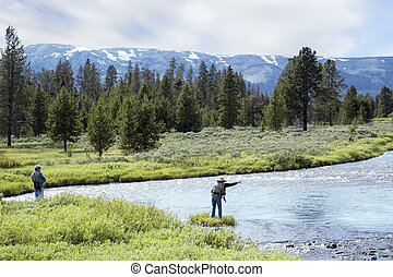 A couple fly fishing together in a mountain lake.