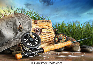 Fly fishing equipment with hat on wooden dock in grass
