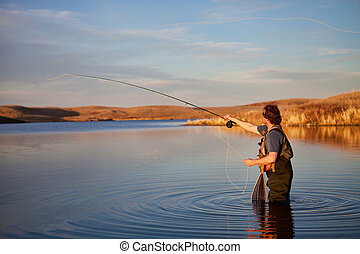 Fly fisherman casting in a lake in golden light.