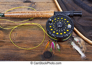 Fly fishing - fly fishing rod and reel on a wet wooden...