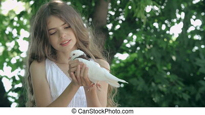 Fly My Bird - Beautiful little girl stroking a pigeon,...