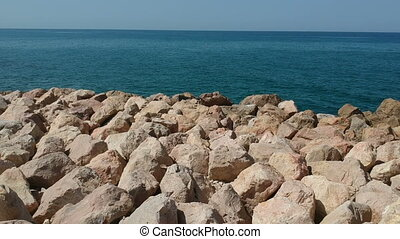 Fly over rocks into the ocean