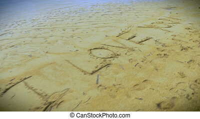 "Fly over shot of """"I Love You"""" written in the sand on the..."
