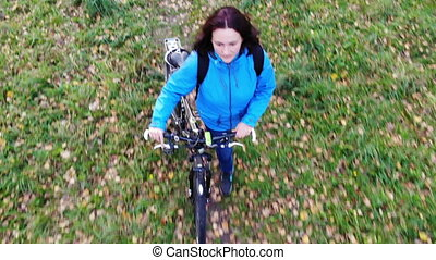 fly over woman with bicycle walking in autumn park, carefree...