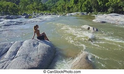 Flycam Approaches Girl Listening to Music among River Rapids...