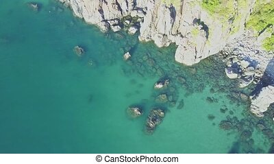Flycam Descends to Turquoise Ocean with Rocky Coastline -...