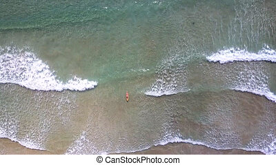 flycam descends to woman surfing on ocean waves under sun rays