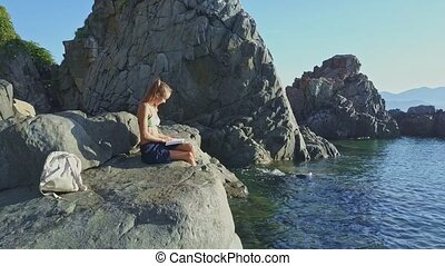 Flycam Moves around Girl Reading Book on Stone near Ocean -...