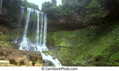 flycam moves from grass bank to rocky against waterfall in...