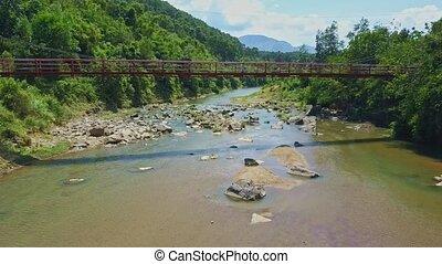 Flycam Moves under Bridge above River against Highlands Sky