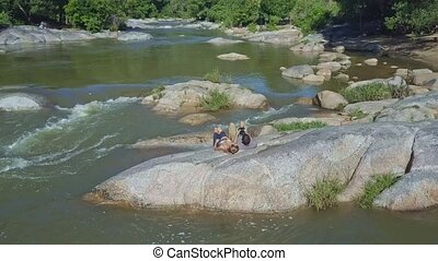 Flycam Removes from Couple Controlling Drone against River -...