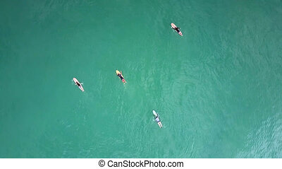 flycam rotates above surfers paddling on boards among ocean...