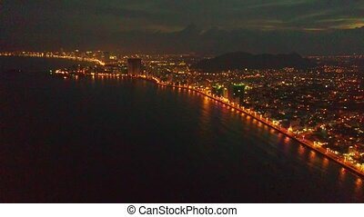 Flycam Shows Dark Ocean Bay at Night Resort City