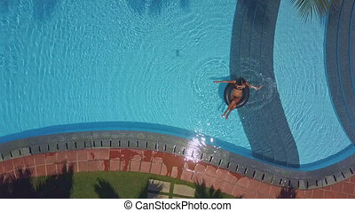 flycam shows hotel pool with lady sitting on buoy - flycam...