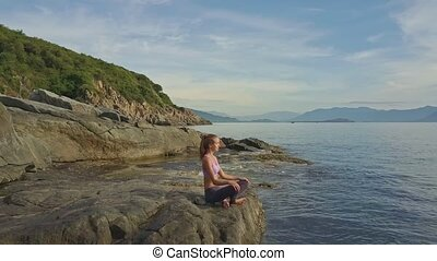 Flycam View Girl Sits in Yoga Pose against Sea Tide to Rocks