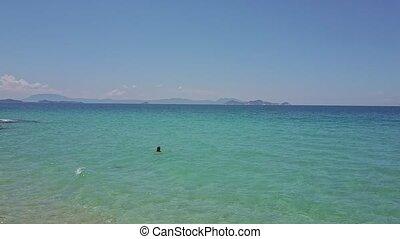 Flycam View Girl Swims in Sea near Rocky Landscape