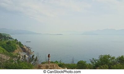 Flycam View Tourist Enjoys Ocean Hilly Landscape from Hill...