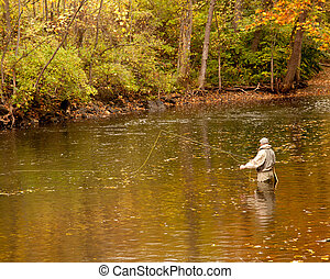 Angler fishing in a deep river in fall with the leaves changing colors