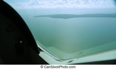 Wide high-angle shot from a plane's window, heading to Lady Elliot of calm green sea water below, and an Island , Great Barrier Reef