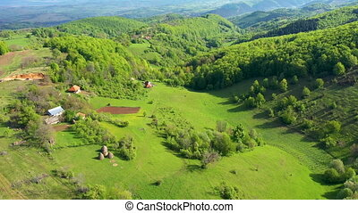 Flying above green countryside hills and village houses,...
