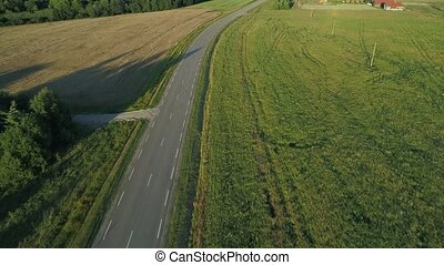 flying above road in fields at evening