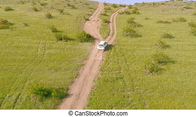 Flying above the car driving offroad through rural countryside