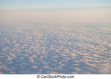 flying above the clouds at sunset landscape from an airplane