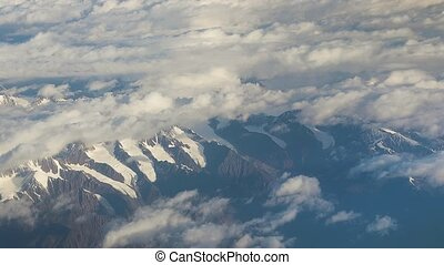 Flying near high mountain ranges of the Himalayas, view through airplane window