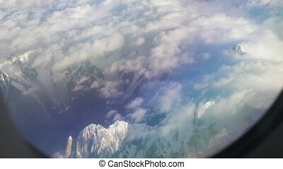 Flying over high mountains of the Himalayas, view through airplane window