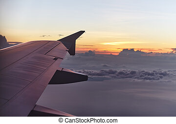 flying aircraft wing on beautiful sunset