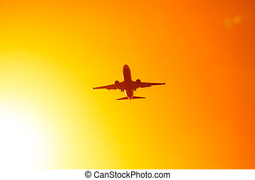 flying airplane in the orange sky sunset