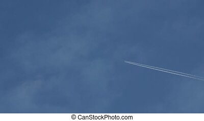 Flying airplane leaving condensation trail in blue sky.