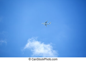 Flying airplane on the blue sky