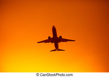 flying airplane silhouette in the orange sky sunset
