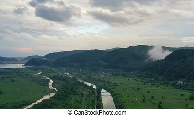 Flying along river, aerial summer landscape of populated ...