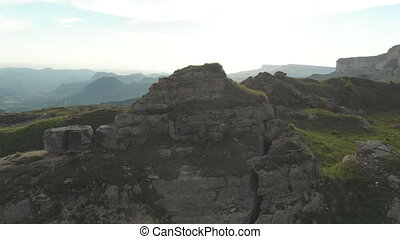 Flying around a large rock formation standing at the foot of...