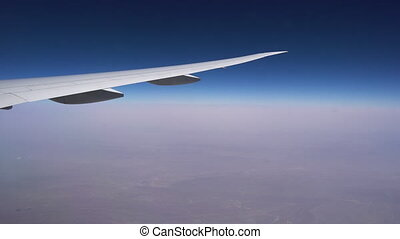 Flying at high altitude. The wing of aircraft on the background of clear sky and endless horizon