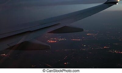 Flying at night, spoilers being deployed - Plane wing...