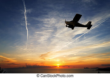 flying at sunset - single engine airplane flying at sunset