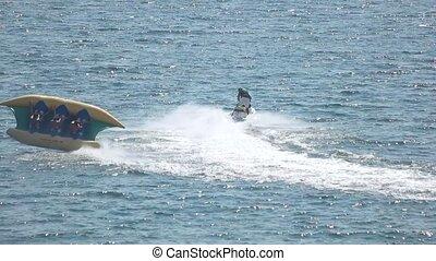 Flying banana boat ride. Jet ski in slow motion.