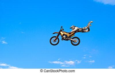 flying biker on a blue sky background
