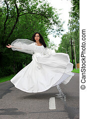 flying bride in white dress outdoors