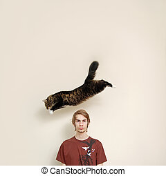 A maine coon cat leaps over a young males head. The person is just staring into the camera.